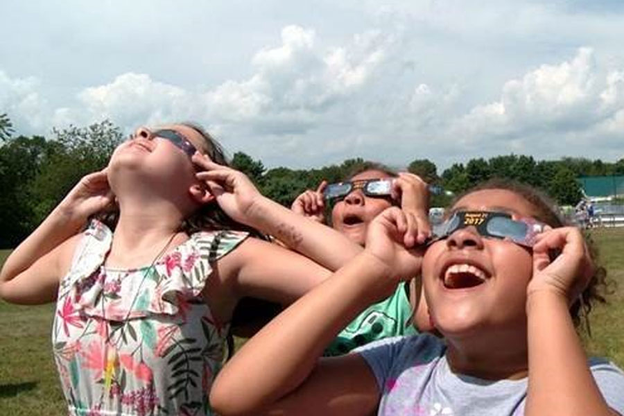 Girls using eclipse glasses to view 2017 solar eclipse