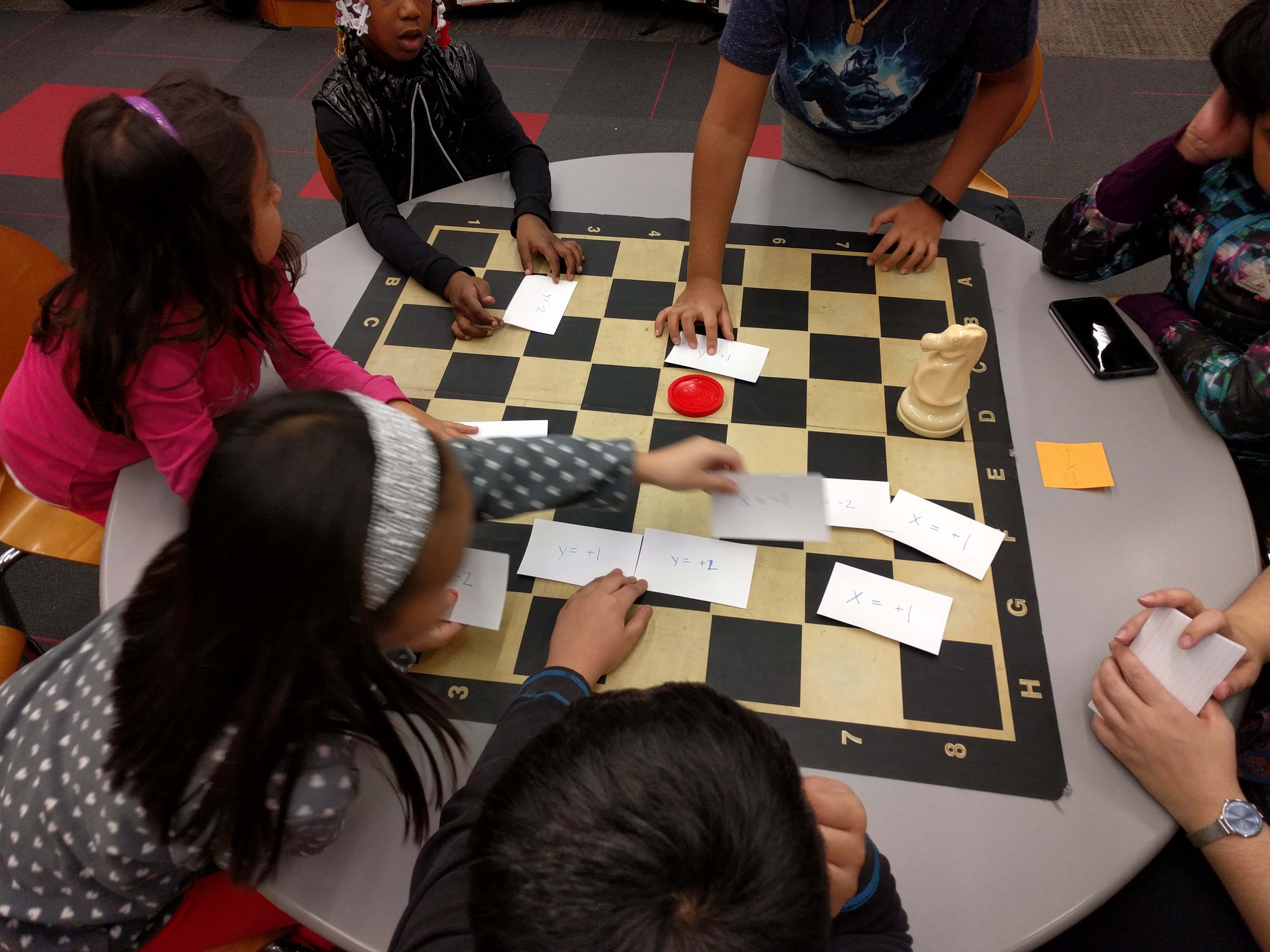 Participants using code written on index cards to move chess and checker pieces.