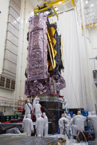 NASA scientists perform environmental testing on the James Webb Space Telescope. Several scientists in protective gear surround the in development telescope.