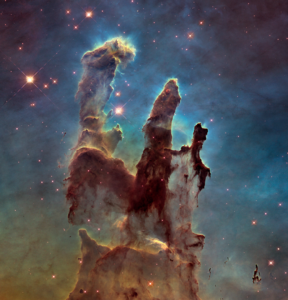 Image shows a cloud of gas extending three tendrils of gas towards the top of the image against a field of stars