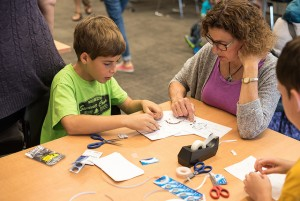 A family working on the robot paper circuit challenge.