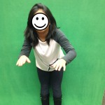 Child poses for green screen image. Face covered for privacy.