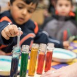 Kids mix different liquids with milk to see different chemical reactions.